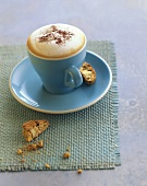 Cappuccino in blue cup & saucer with cantucci (almond biscuits)