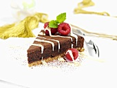 A piece of chocolate fudge cake with raspberries