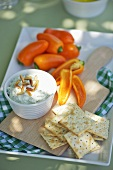 Cream cheese and rocket dip with pine nuts, crakers and peppers