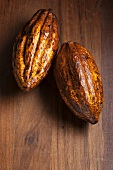 Two cocoa beans on a wooden surface