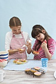 Two girls decorating biscuit lollies with icing sugar