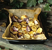 Oven-baked potatoes, onions and garlic on baking tray