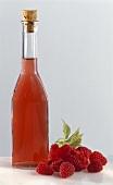 Bottle of raspberry vinegar with fresh raspberries