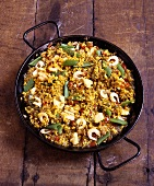 Paella with chicken and shrimps in pan