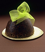 Christmas pudding with green bow on gold plate
