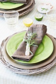 A place setting with a plate in a basket and a napkin decorated with rosemary