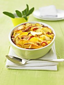 Potato and apple gratin with smoked pork in a baking dish