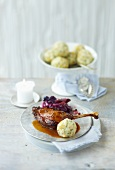 Goose leg braised in malt beer with red cabbage and bread dumplings
