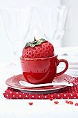 A strawberry-shaped candle in a red espresso cup