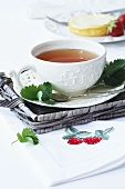 A cup of tea on a wicker tray and a napkin with a strawberry motif