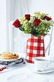 A jug being used as a vase with tea and cake