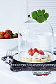 A waffle with cream and strawberries under a cloche