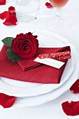 A place setting with a red napkin and a rose