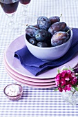 A bowl of damsons on a stack of plates