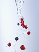 Water and berries pouring out of bottle