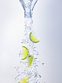 Water and lime wedges pouring out of bottle