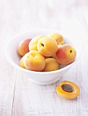 Several apricots in bowl, half an apricot beside it