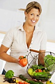 Woman holding wire basket of organic vegetables