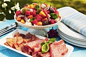 Cold cuts and fruit salad with feta, olives and basil
