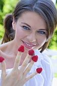 Young woman with raspberries on her fingers
