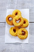 Deep-fried choux pastry rings on piece of kitchen roll