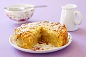 Apple crumble cake with icing sugar, cream jug