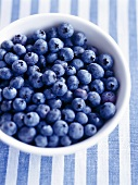 Bowl of fresh blueberries on striped cloth