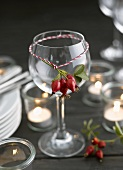 Rose hips tied on wine glass (decorative idea)