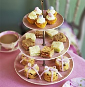 Cupcakes, dainty sandwiches and biscuits on tiered stand