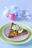 A piece of wholemeal toast topped with herb cream cheese and raw vegetables for Easter