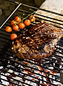 Grilled beef steak with cherry tomatoes on a barbeque