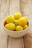 A bowl of yellow plums