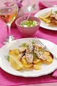 Salmon strips on a bed of fried potatoes