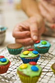 Decorating chocolate cupcakes with chocolate beans