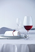 Glass of red wine on table laid in white