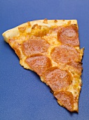 A slice of salami pizza on blue background