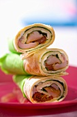 Three wraps filled with salad leaves, ham and dried tomatoes