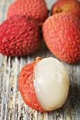 Lychees on wooden background, one partly peeled