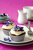 Carrot cupcakes with cream icing and edible flowers