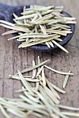 Dried rosemary needles with a wooden spoon