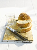 White bread slices, knife and empty glass on a cutting board
