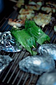 Halibut wrapped in banana leaves, potatoes in aluminum foil and eggplant rolls on the grill