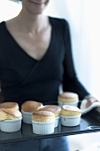 A lady serving vanilla souffles on a serving tray