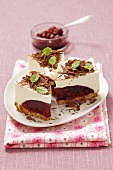 Three slices of cheesecake with cherry jam and chocolate curls