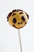 A yellow cake pop with a face