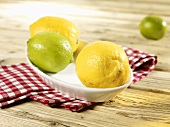 Lemons and limes in a bowl on a checked cloth