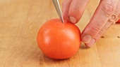 A fresh tomato being slit with a knife