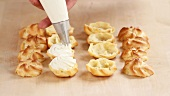 Profiteroles being filled with cream