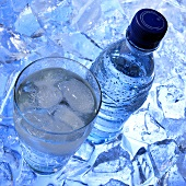 Mineral water in glass and bottle on ice cubes