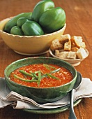 Red pepper soup with strips of green pepper; croutons